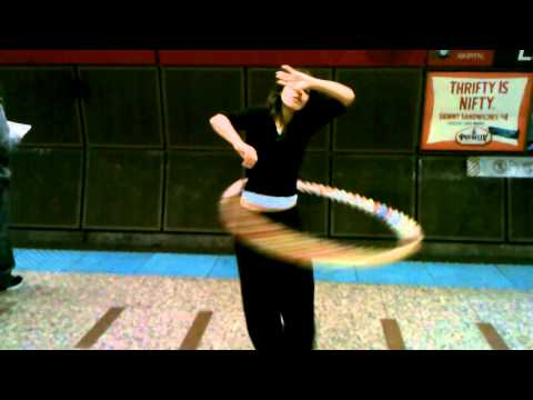 Cute Hula Hoop Girl at L station in Chicago w/music playing.