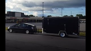 Small car towing an enclosed trailer