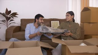 A young Indian couple unpacking cardboard boxes for their house interiors stuff for new apartment