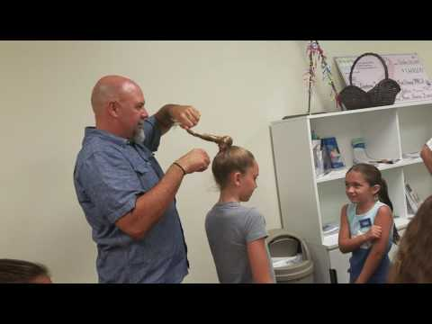 Dad giving his daughter a dizzy bun in her hair