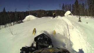 ski-doo in deep powder wood path