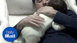 A dad comforts his crying baby by getting in her cot