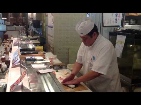A japanese guy showing off his sushi-making skills