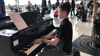 "Volunteer teen pianist, evan brezicki, performs ""the greatest showman"" medley at the charlotte douglas international airport in charlotte, nc. ; ""a million d..."