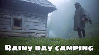 Tarp camping on a raİny day near an abandoned log cabin