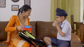 Indian beautiful mother happily packing her son's backpack for school - Sikh family