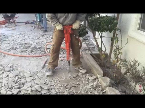 Jack Hammering Concrete With High Powered Air Jack Hammer
