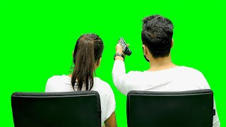 Couple watching television against the chroma screen and changing channels