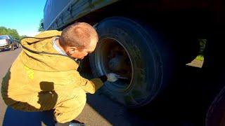Стажер меняет колесо на полуприцепе, фуре.