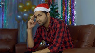 Sad Indian guy sitting alone on a sofa with colorful Christmas decorations in the background