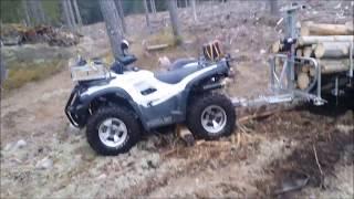 Fyrhjuling med huggarvagn i skogen i mindre bra terräng.