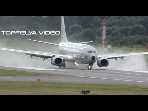 Steep Bank to final and powerful reverse thrust spray Boeing P-8 Poseidon landing on wet runway