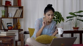 Smiling young Indian woman working from home on her laptop - office work. Work from home concept