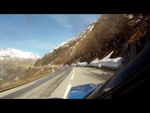 Ferrari 599GTB & Lotus Evora driving up Furka pass in Swiss Alps