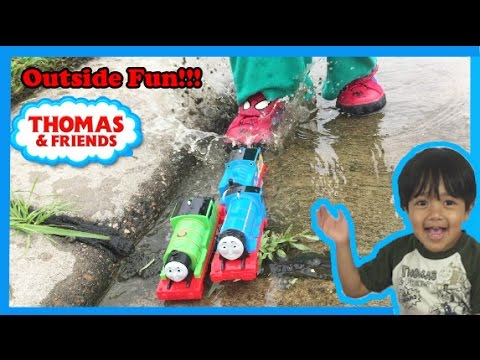 Ryan plays with Thomas and Friends toy trains outside!