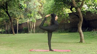 A young girl practicing natrajasana / lord of the dance yoga pose outside in a park
