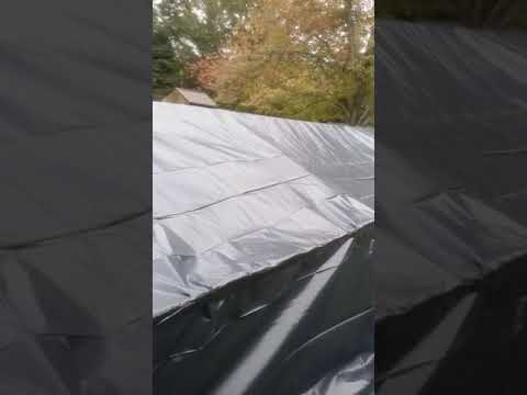 Constructing haunted house maze using tents and black rolled plastic the beginning