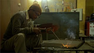 A middle-aged Indian worker welding metal at a factory