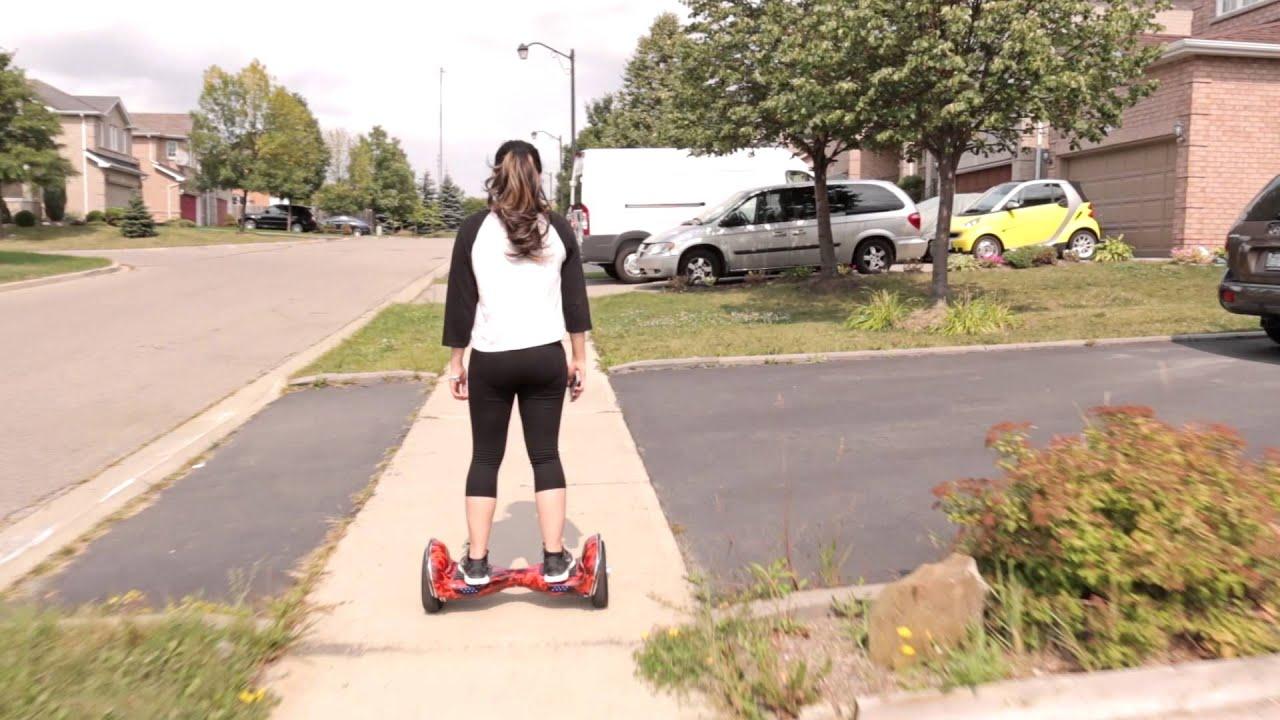Una ragazza viene ritratta di spalle mentre si sposta sul suo hoverboard con fantasie rosse e nere