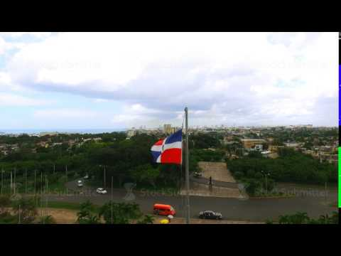 The camera flies past a waving flag of the Dominican Republic