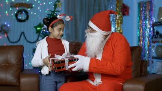 Smiling Indian girl getting a surprise Christmas present from Santa Claus in India