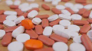Close pan shot of medical pills lying on the table