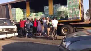 People loot a Heineken truck in South Africa