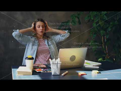 Young blond woman is sitting in office working with computer. She is tired so she is touching her