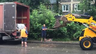 Экскаватор-погрузчик разгружает фуру полетными вилами в Калуге