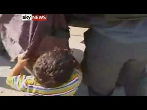 Palestinian boy begs Israeli soldiers not to take his Father for stealing him fresh water.flv