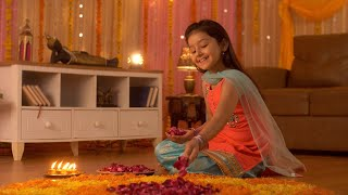 A cute little girl wearing a suit and decorating flower's rangoli with rose petals - Tradition during the Indian festivals