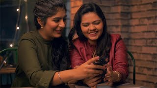 Two young girls laughing and watching funny videos on the smartphone - lifestyle concept