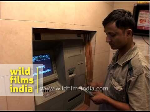 Man withdrawing money from bank ATM in India