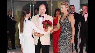 Princess Charlene holds crimson blooms for her stunning entrance to 70th Monaco Red Cross Ball with