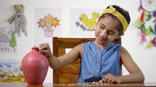 Indian girl inserting coins into a clay money bank (Gulak) - savings concept