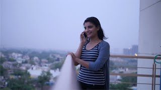 Pretty young Indian girl standing in the balcony and speaking on the phone - Enjoying the view from the balcony