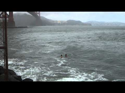 Australian tourists swim westward under the Golden Gate Bridge out to the Pacific