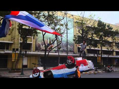 Thai protester waves flag on wrecked cop car 2014