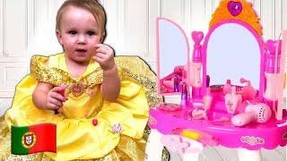 Cinco Crianças brincam com uma mesa de maquiagem de brinquedo