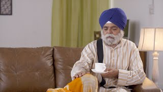 Sikh family early morning scenario: Daughter-in-law serving tea to father-in-law.  Old sikh man reading Gutka