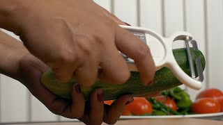A woman peeling a cucumber at a kitchen counter