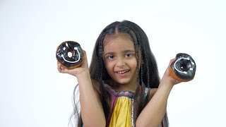 Young pretty girl happily playing with chocolate donuts against the white background