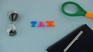 "Closeup shot of a word ""TAX"" composed of colorful plastic letters on a blue platform"