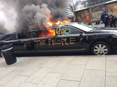 "Burning limo from the #DisruptJ20 protests, has ""WE THE PEOPLE"" and the Anarchy symbol spray painted on it"