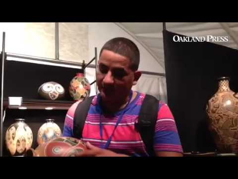 Luis Gutierrez came from Nicaragua. He explained that the parrots on his pottery were inspired by hi