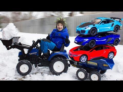 Мальчик на синем тракторе помогает папе и находит в снегу новые машинки