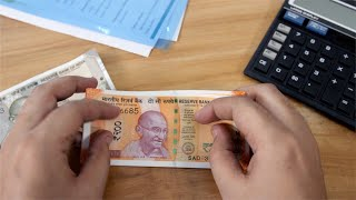 Bank manager counting Rs 200 Indian currency and keeping on the table