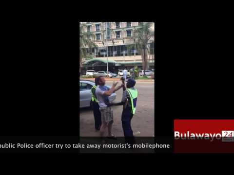 Zimbabwe Republic Police traffic cops try to take away motorist's mobilephone