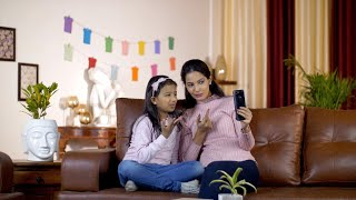 A young mother and her daughter waving a 'Hi' while having a conversation on a video call