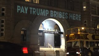 """A Washington-based artist and filmmaker briefly illuminated U.S. President Donald Trump's Washington hotel with projected messages, including """"pay Trump bribes here"""" and """"emoluments welcome."""""""